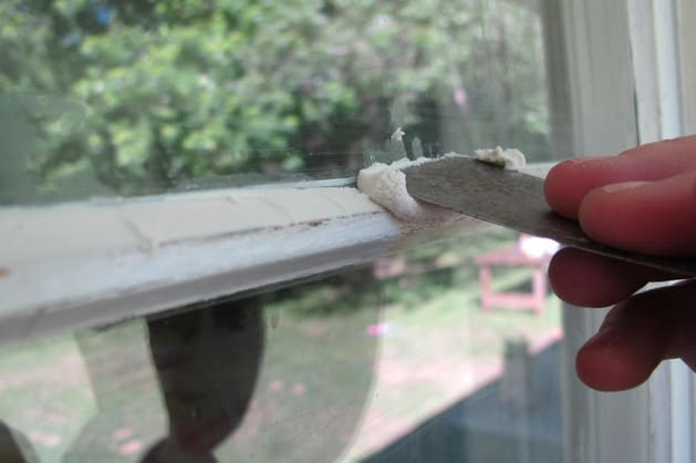 glazier applying putty on window